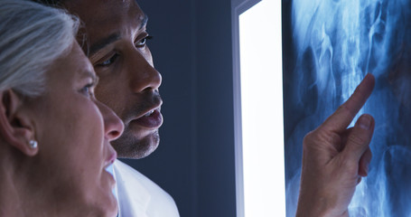 Close view of young male doctor and senior colleague looking at x-ray of patients spine. Close up of millennial black doctor consulting with senior colleague over x ray of spinal bones