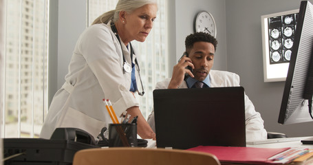 Young african-american doctor using cellphone inside medical office. Senior female doctor working with younger colleague on patient medical file