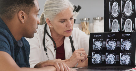 Close up of doctor consulting with patient on his concussion looking at ct scans of his brain