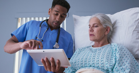Young african-american RN and senior patient looking at tablet computer at hospital. Male registered nurse showing ill elderly woman electronic pad