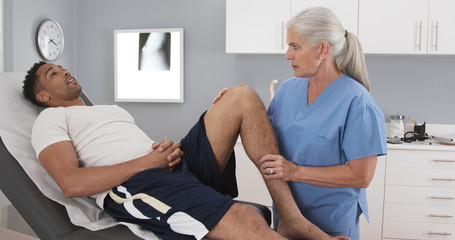 Male millennial black patient at clinic with injured knee assisted by senior doctor. Elderly female doctor assessing mans leg injury