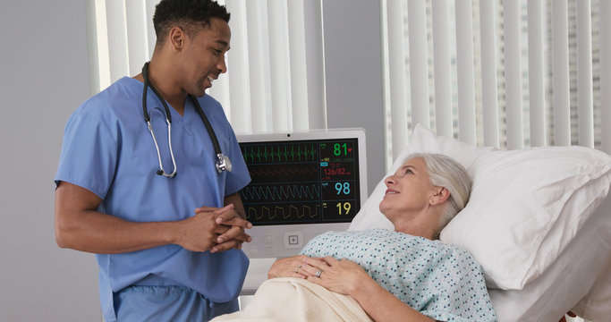 Sick senior woman resting in hospital bed after surgery talking to young male nurse. Portrait of african-american nurse assisting ill female patient lying in bed