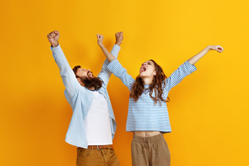 young happy couple won emotionally celebrating win on colored yellow background