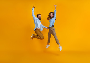 couple of emotional people man and woman jumping on yellow background. Wall mural