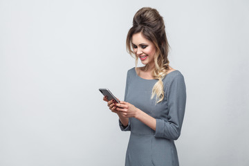 Portrait of happy beautiful blogger teenager wearing in grey dress with pigtail on head standing, using smartphone and texting message with toothy smile. Indoor, isolated, studio shot, grey background
