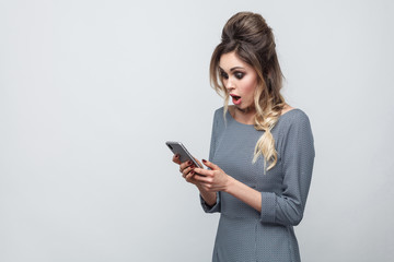 Side view of shocked beautiful blogger teenager wearing in grey dress with pigtail on head standing, using smartphone and watching video with amazed face. Indoor, isolated,studio shot, grey background