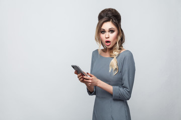 Portrait of shocked beautiful blogger teenager wearing in grey dress with pigtail on head standing, using smartphone and watching video with amazed face. Indoor, isolated, studio shot, grey background