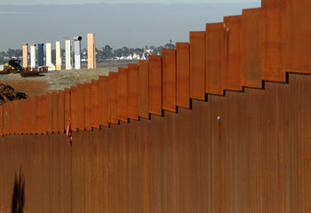 The prototypes for U.S. President Donald Trump's border wall are seen behind the border fence between Mexico and the United States, in Tijuana