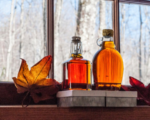 Maple syrup in old bottles at window