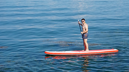 Friendly young man active with paddel-board on Lake Constance