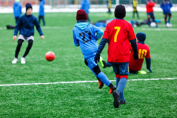 Boys  in red and blue sportswear plays soccer on green grass field. Youth football game. Children sport competition, kids plays outdoor, winter activities, training