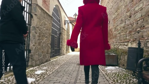 a follow angle of two models, man and woman, walking down a cobble