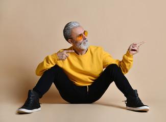 Portrait of gray hair senior millionaire man in yellow sunglasses stylish fashionable men