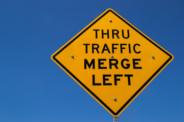 """The """"Thru Traffic Merge Left"""" street sign with brilliant blue skies in the background."""