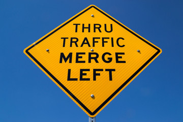 "The ""Thru Traffic Merge Left"" street sign with brilliant blue skies in the background."