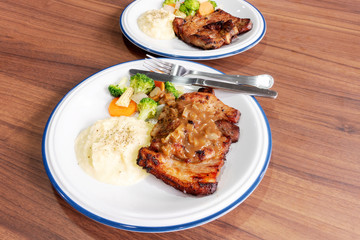 Pork steak with vegetables On the wood background