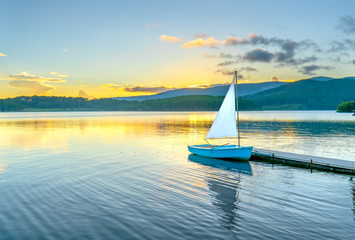 Lonely sailboat in the beautiful sunset with sun stars shines from sky and the surface of the lake is calm and peaceful when watching them Wall mural