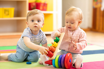 funny babies boy and girl playing on floor in game room in nursery