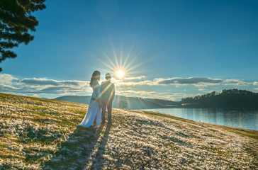 Da Lat, Vietnam - November 29th, 2018: Silhouette of happy lovers together to welcome the dawn on the pink grass in the romantic morning sun in the highlands of Da Lat, Vietnam
