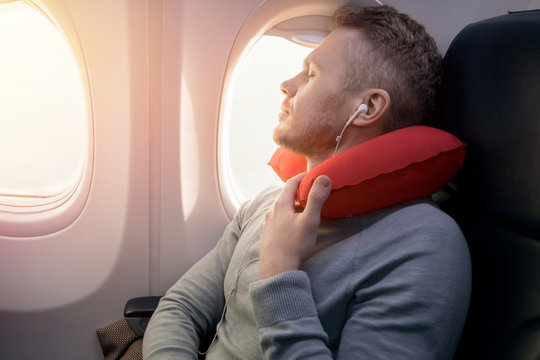 Male passenger of airplane listens to music and enjoys pillow for sleeping in chair.