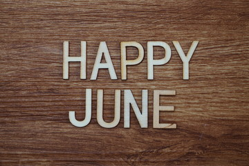 Happy June text message on wooden background