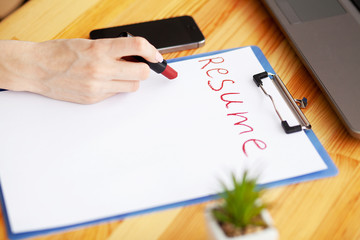Job search. Female hand writes resume with lipstick on white sheet of paper. Wooden office desk with laptop, smartphone and supplies