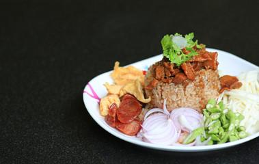 Obraz Fried rice Shrimp paste with pork and fried egg in plate on black table. Thai food (Kao Cluk Ka Pi). - fototapety do salonu