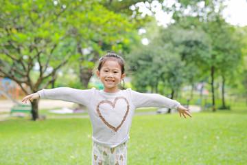 Portrait of smiling little Asian children opened her hands in the green garden.