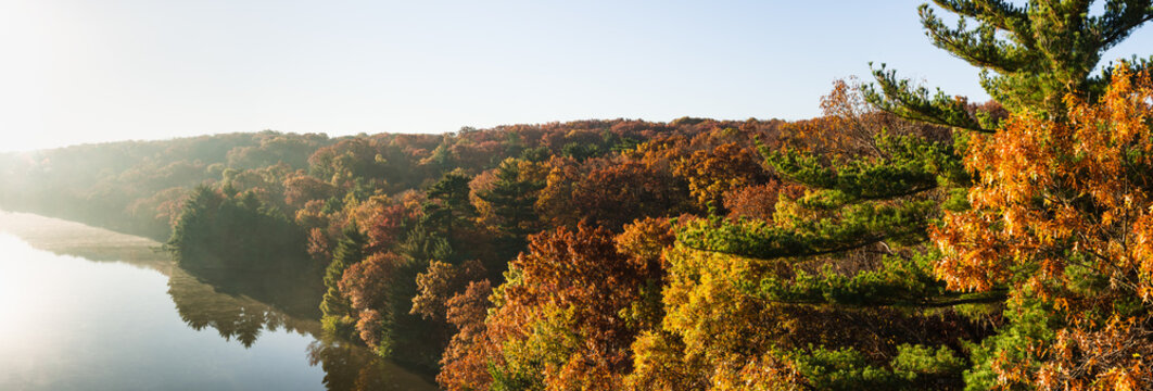 Autumn colors on the Illinois River as the morning sun lights up the tree tops.  Starved Rock State Park, Illinois, USA