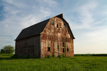 Old wooden red barn in the rural countryside as the sun starts to set.  LaSalle County, Illinois, USA