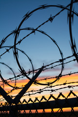 Dramatic sunset with chain link fence and razor wire silhouette.