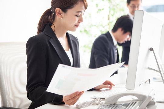 書類を確認しながらデータ入力をおこなう女性会社員