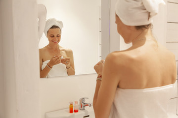 Beautiful young woman in a white towel in the bathroom in front of the mirror, use cosmetics. home care concept
