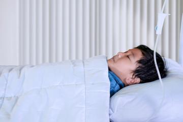 Pale little boy is lying in the clinic
