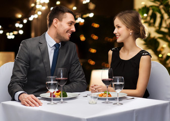 people and leisure concept - smiling couple with food and non-alcoholic red wine talking at restaurant over festive lights on background
