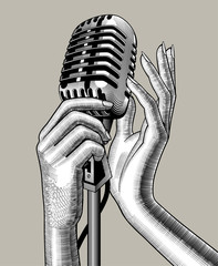 Female hands with a retro microphone