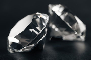 close up of two clear diamonds on black background