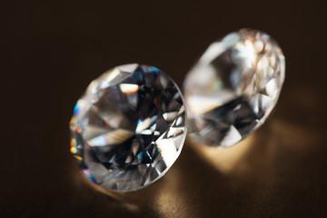 close up of big transparent diamonds on golden dark background