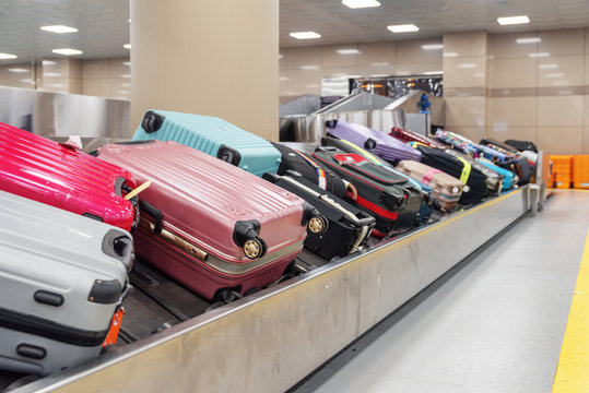 Pink, blue and violet suitcases on luggage conveyor belt