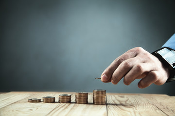 Businessman stacking coins. Budget and finance concept