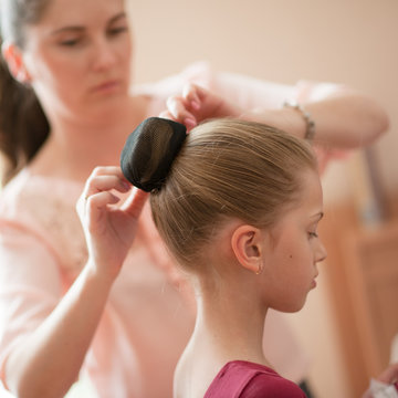 caring young mother woman fixing her little thin girl daughter hair bun
