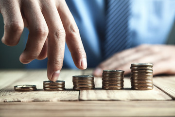 Hand with fingers stepping on coins. Financial growth concept