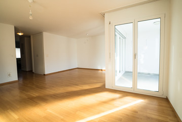 Obraz bright new living room in an empty apartment with french doors and parquet wooden floors - fototapety do salonu