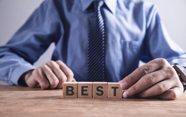 Businessman holding wooden cube with Best word.