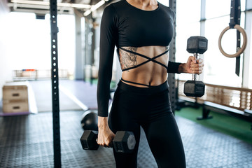 Slim body of a young woman with tattoo in a black sportswear that builds up muscles with dumbbells in the gym