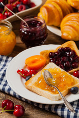 Breakfast. Toasts with cherry or peach jam and fresh fruit.