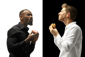 Men eating a hamburger and donut on a black and white background. The happy afro and caucasian men. The burger, fast, unhealthy food concept