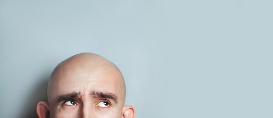 Emotional portrait of surprised bald man. half-face. Copyspace for text.