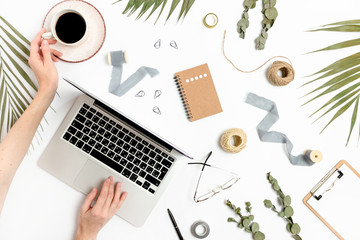 Woman using laptop. Workspace with green leaves, mug of coffee, stationery and accessories on a white background