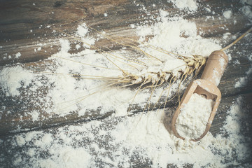 Fresh flour, wooden spoon, spike in vintage style on a wooden table